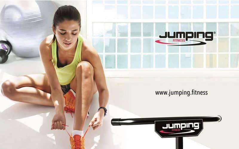 Junge, sportliche Frau sitzt auf dem Boden und bindet sich die Schuhe für ihren Fitnesskurs Jumping Fitness zu.