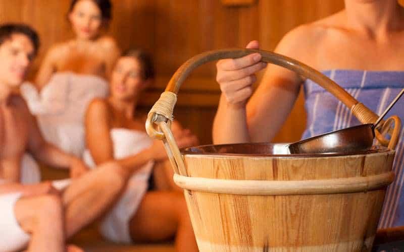 Drei Frauen und ein Mann in der Sauna. Im Vordergrund ein Aufgusseimer aus Holz