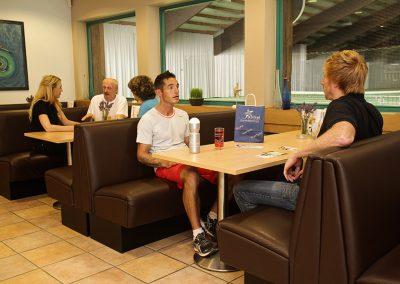 Zwei besetzte Tische in der Bistro-Lounge im Seestern Fitnessclub Süd. An dem hinterem Tisch findet ein Beratungsgespräch zwischen Trainerin und einem Ehepaar statt. An dem vorderen Tisch unterhalten sich zwei Sportler und nehmen ein Erfrischungsgetränk zu sich.