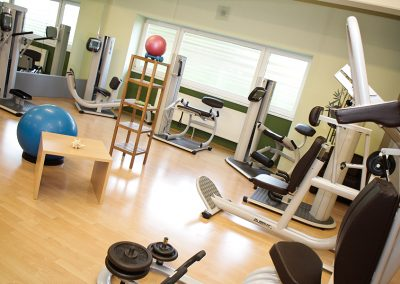 Dr. Wolff Sportgeräte für Zirkeltraining im Gesundheitssport. Sechs Geräte stehen im Halbkreis angeordnet nebeneinander. In der Mitte steht ein Tisch, ein Gesunheitsball und Hanteln.