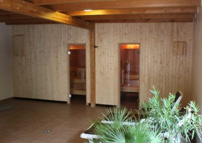 Saunabereich mit Eingang zur Finnischen- und Softsauna. Die Kabinen sind mit hellem Holz verkleidet und davor stehen zwei Liegen zum Erholen und grüne Palmen.