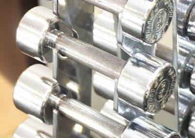 Kleine silberne Hanteln für Krafttraining übereinander gestapelt.