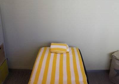 Massageliege im ruhigen Massageraum mit Nackenrolle und gelb-weiß gestreiftem Handtuch als Unterlage.