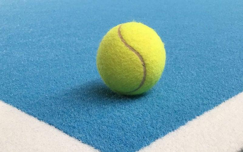 Tennisball auf Grundlinie eines blauen Tennisplates aus Teppich
