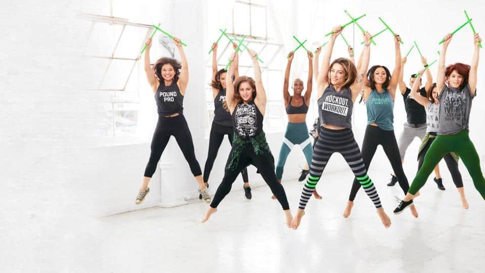 Pound Fitness - Frauen mit grünen Drumsticks springen in die Luft